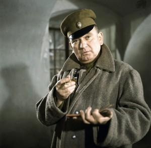 """Szene aus der unvergessenen TV-Serie """"Die Abenteuer des braven Soldaten Schwejk"""" mit Fritz Muliar (Bild) in der Hauptrolle. Josef Schwejk ist, wie er sagt, """"versehentlich"""" in österreichische Kriegsgefangenschaft geraten. Immerhin, er wurde, angetan mit einer russischen Uniform, von einer Patrouille aufgegriffen. Das kann ihn den Kopf kosten.   Abdruck mit freundlicher Genehmigung des ZDF."""