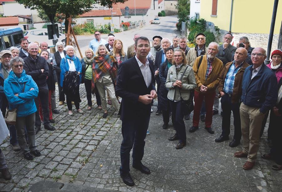"""Benedikt Feser (M) präsentiert das baldige """"Haus des Dialekts"""" in Büchold den Teilnehmern des """"Tages des Dialekts"""". Die ihrerseits beobachten ganz genau, ob der Fotograf auch richtig fotografiert."""